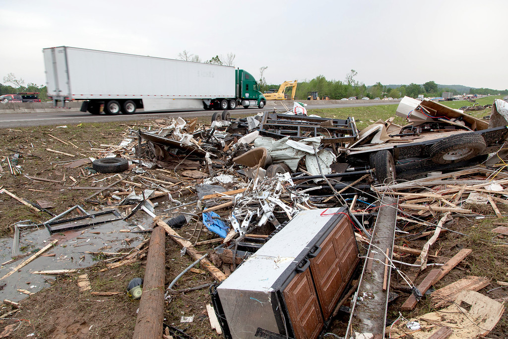Description of . Piles of debris sits along side of Interstate 40 westbound as traffic flows slowly Monday, April 28, 2014 in Mayflower, Ark., after a tornado struck the town late Sunday. Mayflower was hit hard Sunday after a tornado system ripped through several states in the central U.S. and left more than a dozen dead in a violent start to this year's storm season, officials said.  (AP Photo/Karen E. Segrave)