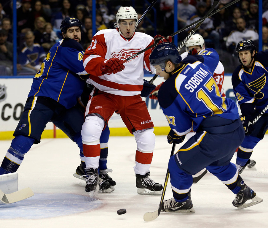 Description of . St. Louis Blues' Vladimir Sobotka, of the Czech Republic, controls the puck as teammate Roman Polak, left, of the Czech Republic, and Detroit Red Wings' Valtteri Filppula, center, of Finland, look on during the first period of an NHL hockey game Saturday, Jan. 19, 2013, in St. Louis. (AP Photo/Jeff Roberson)