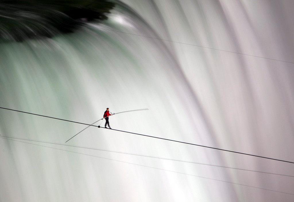 . In this June 15, 2012 file photo, Nik Wallenda walks over Niagara Falls on a tightrope in Niagara Falls, Ontario. Wallenda finished his attempt to become the first person to walk on a tightrope 1,800 feet across the mist-fogged brink of roaring Niagara Falls. The seventh-generation member of the famed Flying Wallendas had long dreamed of pulling off the stunt, never before attempted. (AP Photo/The Canadian Press, Frank Gunn, File)