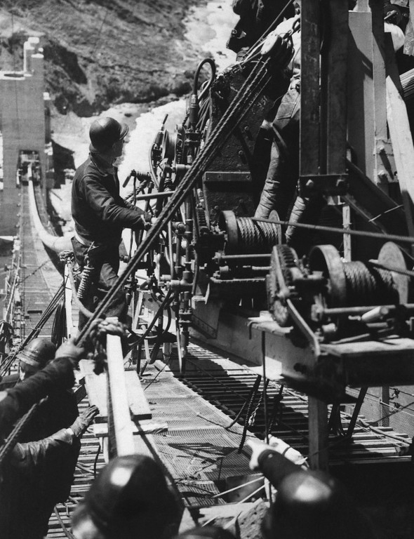 Description of . Workmen with an intricate mechanism swung high above the rocky shores of San Francisco's Golden Gate on June 6,1936. The workmen are typing together the myriad strands of the 36 1/2 inch cables that will support the Golden Gate Bridge. (AP Photo)