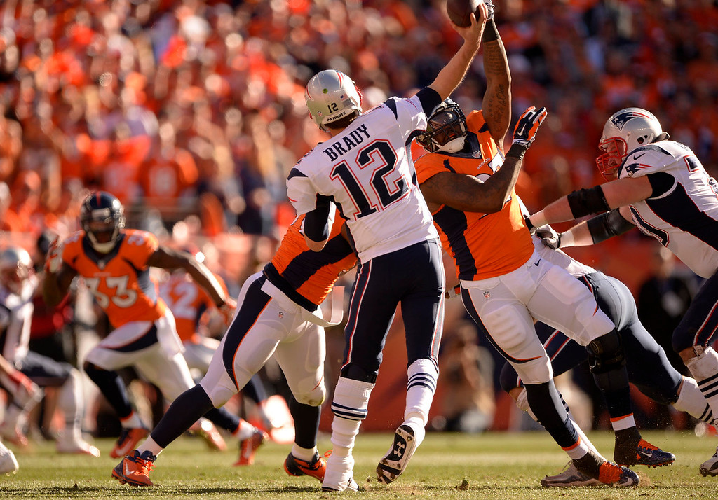 Description of . Denver Broncos defensive end Malik Jackson (97) puts pressure on New England Patriots quarterback Tom Brady (12) during the first quarter. The Denver Broncos vs. The New England Patriots in an AFC Championship game  at Sports Authority Field at Mile High in Denver on January 19, 2014. (Photo by John Leyba/The Denver Post)