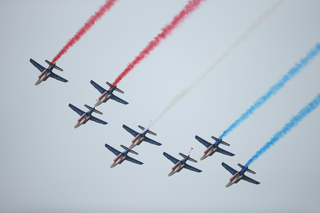 Description of . French planes trailing red, white and blue pass over the main international ceremony commemorating the 70th anniversary of the D-Day invasion with 17 heads of state at Sword Beach on June 6, 2014 at Ouistreham, France.  (Photo by Sean Gallup/Getty Images)