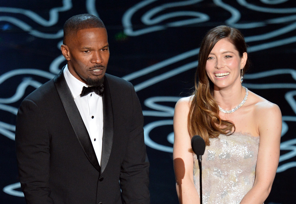 Description of . Actors Jamie Foxx and Jessica Biel speak onstage during the Oscars at the Dolby Theatre on March 2, 2014 in Hollywood, California.  (Photo by Kevin Winter/Getty Images)
