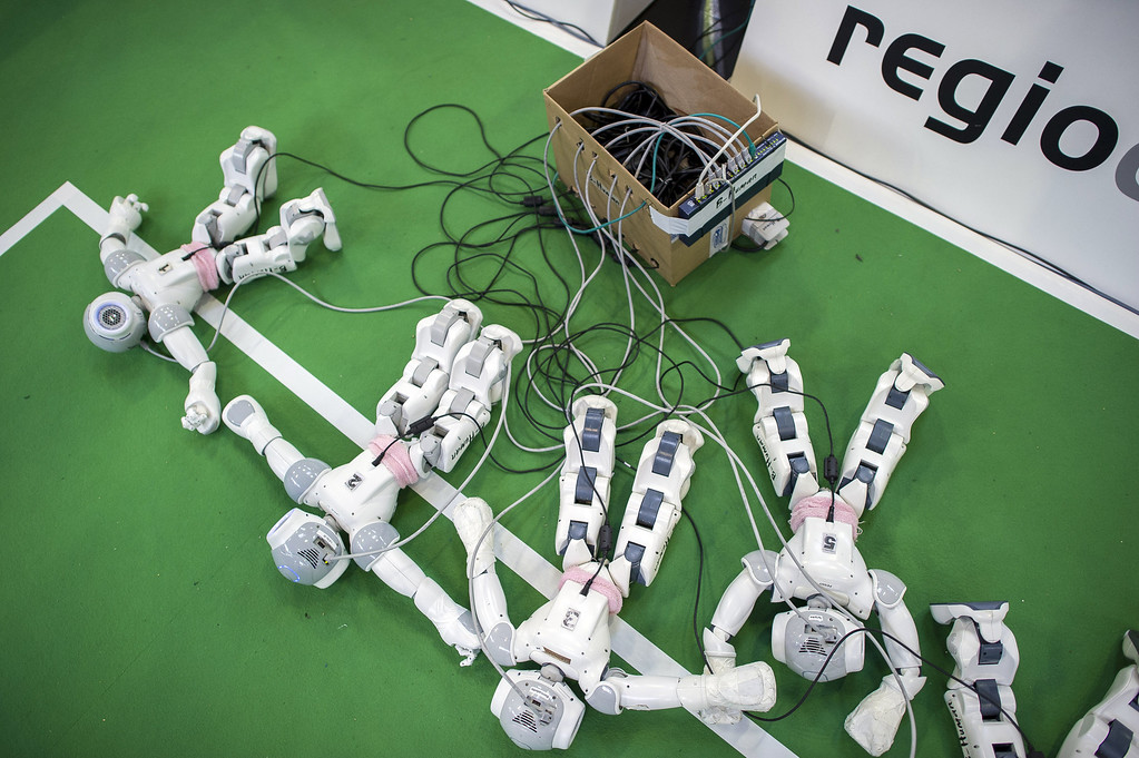 Description of . MAGDEBURG, GERMANY - APRIL 26:  Robots charge by the play field at the 2013 RoboCup German Open tournament on April 26, 2013 in Magdeburg, Germany. The robots, which are a model called Nao, manufactured by Aldebaran Robotics, perform autonomously and communicate with one another via WLAN. The three-day tournament is hosting 43 international teams and 158 German junior teams that compete in a variety of disciplines, including soccer, rescue and dance.  (Photo by Jens Schlueter/Getty Images)