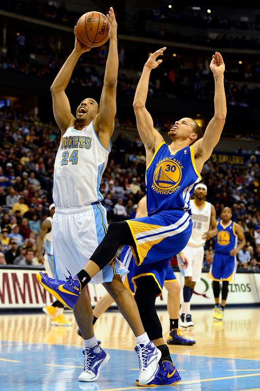 Description of . Denver Nuggets point guard Andre Miller (24) skies for a rebound over Golden State Warriors point guard Stephen Curry (30) during the first half at the Pepsi Center on Sunday, January 13, 2013. AAron Ontiveroz, The Denver Post