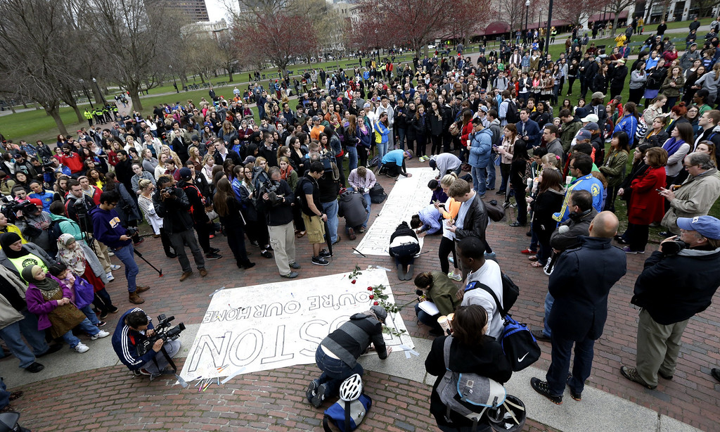 Description of . People congregate at Boston Common for a vigil for the victims of the Boston Marathon explosions, Tuesday, April 16, 2013, one day after bombs exploded at the finish line of the Boston Marathon. (AP Photo/Julio Cortez)