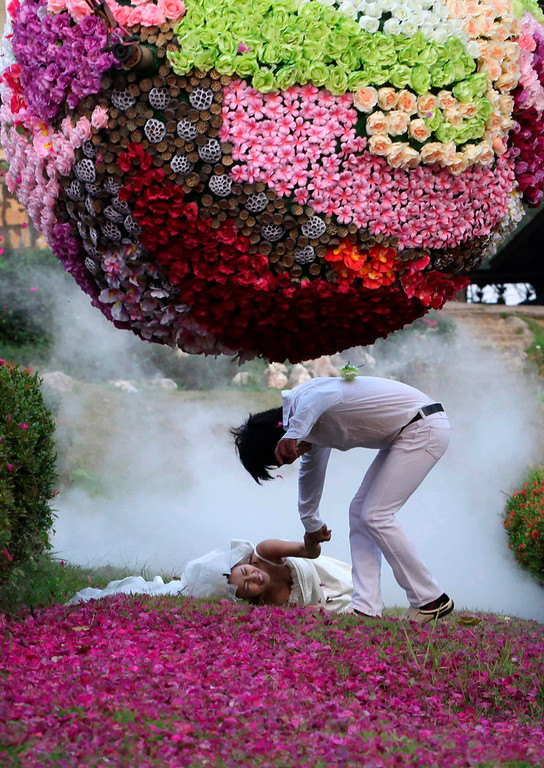 Description of . Thai bride Chutima Imsuntear, 37, falls as she runs with groom Sopon Sapaotong (R), 41, during a wedding ceremony ahead of Valentine's Day in Prachin Buri province, east of Bangkok February 13, 2013. Three Thai couples took part in the wedding ceremony arranged by a Thai resort, aimed to strengthen the relationships of the couples by doing fun activities.   REUTERS/Kerek Wongsa