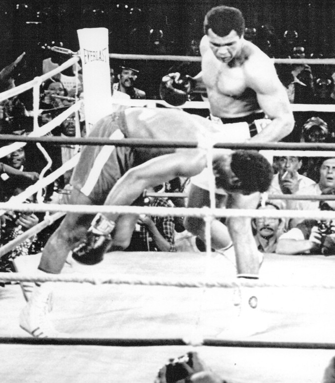 Description of . Ali wins Back The Crown--George Foreman Falls toward the canvas as his defense of the world heavy weight title ends in an eighth-round knockout by Muhammad Ali Oct. 30 in Kinshasa, Zaire. 1974. Credit: AP Wirephoto
