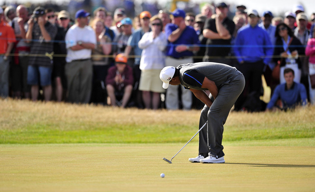 Description of . US golfer Tiger Woods reacts after missing a putt on the 10th green during the third round of the 2013 British Open Golf Championship at Muirfield golf course at Gullane in Scotland on July 20, 2013.  GLYN KIRK/AFP/Getty Images