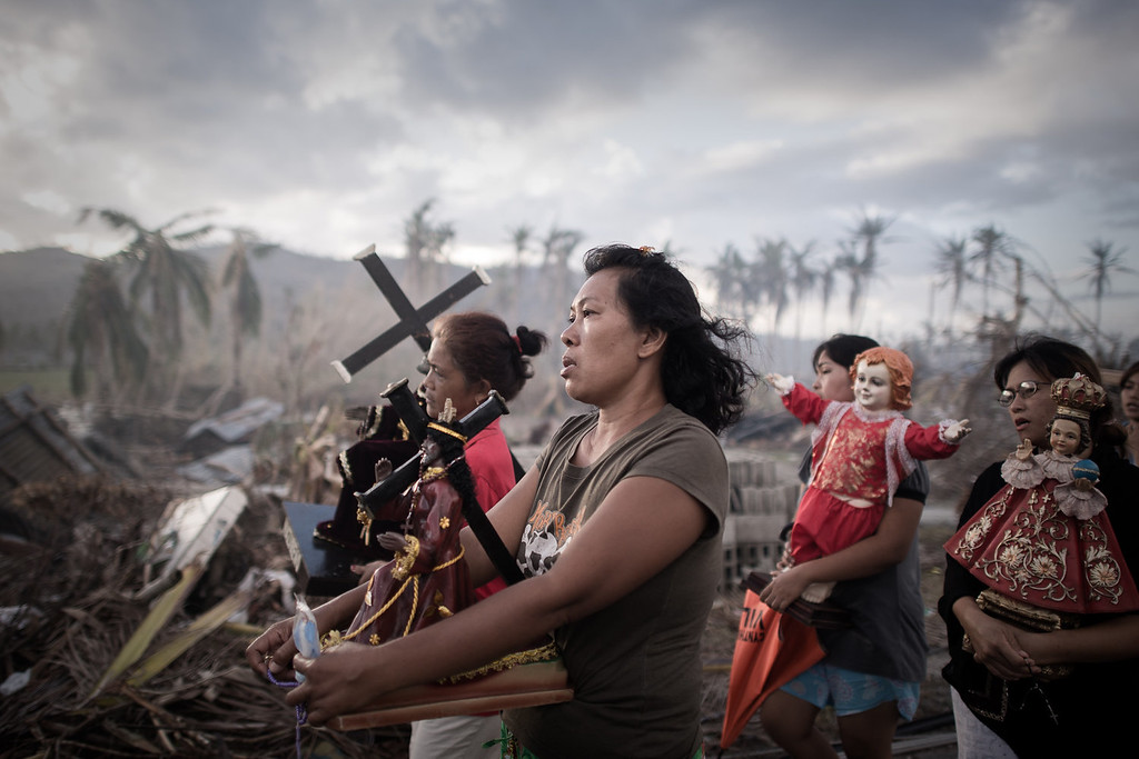 Description of . Survivors of Super Typhoon Haiyan march during a religious procession in Tolosa on the eastern Philippine island of Leyte on November 18, 2013 over one week after Super Typhoon Haiyan devastated the area.  The United Nations estimates that 13 million people were affected by Super Typhoon Haiyan with around 1.9 million losing their homes.   PHILIPPE LOPEZ/AFP/Getty Images