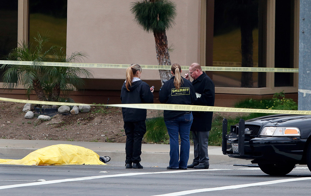 Description of . Investigators stand next to a tarp covered body in Orange, Calif., Tuesday, Feb. 19, 2013. (AP Photo/Jae C. Hong)