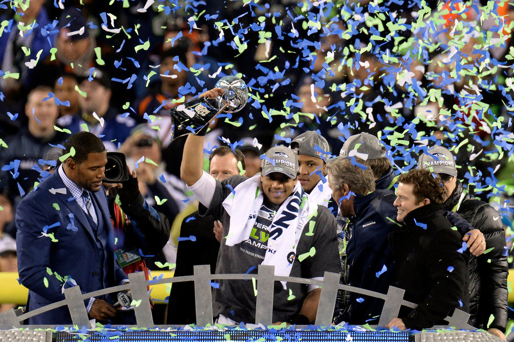 Description of . Seattle Seahawks quarterback Russell Wilson (3) holds up the Vince Lombardi Trophy after the Seahawks defeated the Broncos 43 to 8.  The Denver Broncos vs the Seattle Seahawks in Super Bowl XLVIII at MetLife Stadium in East Rutherford, New Jersey Sunday, February 2, 2014. (Photo by Hyoung Chang//The Denver Post)