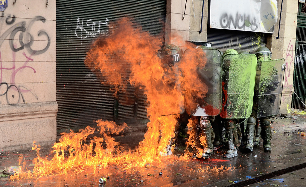 Description of . Students clash with riot police during a protest to demand Chilean President Sebastian Pinera\'s government to improve the public education quality, in Santiago, on April 11, 2013. PABLO TAPIA/AFP/Getty Images