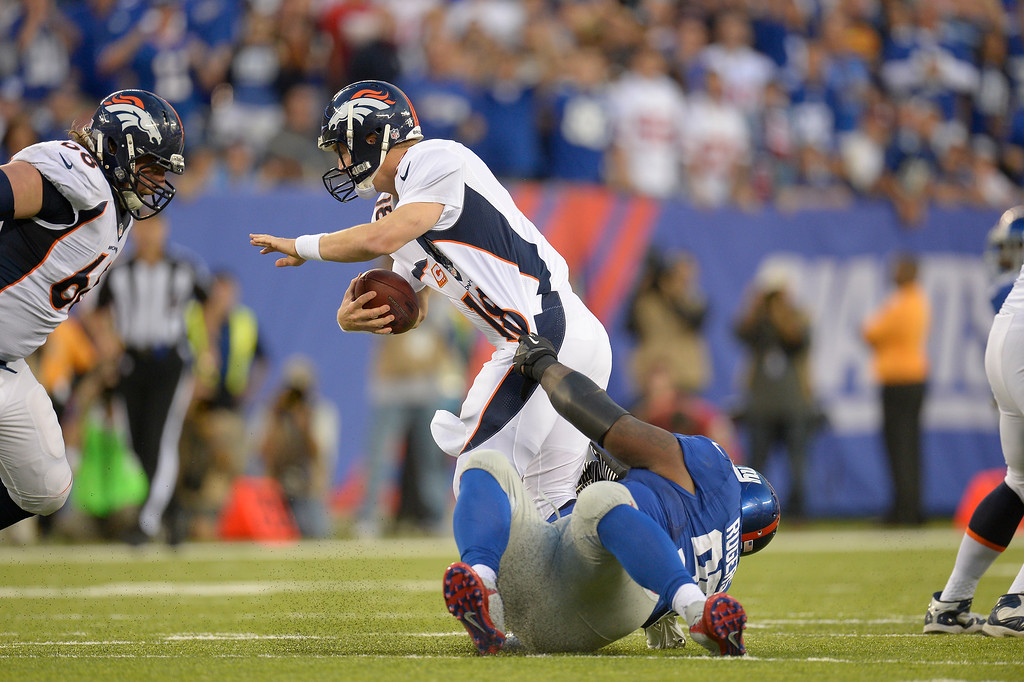 Description of . Denver Broncos quarterback Peyton Manning (18) escapes the grasp of New York Giants defensive tackle Shaun Rogers (95) to avoid a sack during the third quarter September 15, 2013 MetLife Stadium. (Photo by John Leyba/The Denver Post)