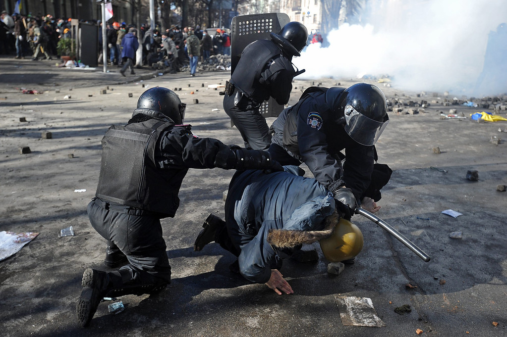 Description of . Riot police detains a protester during an anti-government protest in downtown Kiev, Ukraine, 18 February 2014. A least three protesters were killed in clashes with police on 18 February, Ukrainian opposition activists say. Violence erupted in the Ukrainian capital after anti-government protesters broke through a police cordon in front of parliament. Protester marched toward the parliament to demand constitutional reforms that would curb the powers of President Viktor Yanukovych. Ukraine has been mired in political crisis since November after the government backed away from a trade agreement with the European Union and signed a 15-billion-dollar loan deal with Russia instead.  EPA/ALEXEY FURMAN