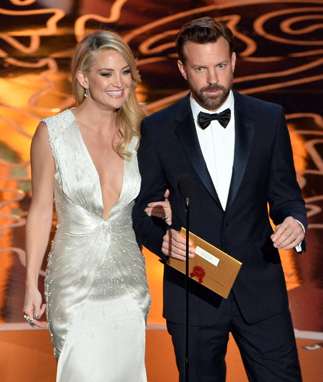 Description of . Actors Kate Hudson and Jason Sudeikis speak onstage during the Oscars at the Dolby Theatre on March 2, 2014 in Hollywood, California.  (Photo by Kevin Winter/Getty Images)