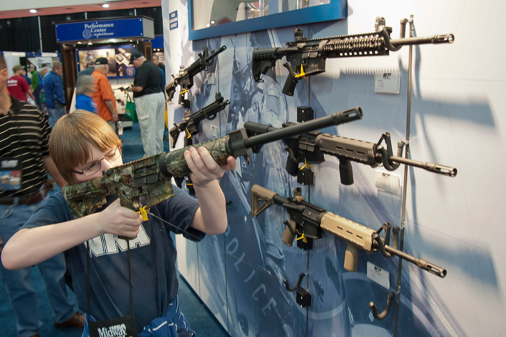 Description of . A young man who chose not to give his name sizes-up an assault style rifle during the National Rifle Association's annual convention Friday, May 3, 2013 in Houston. (AP Photo/Steve Ueckert)