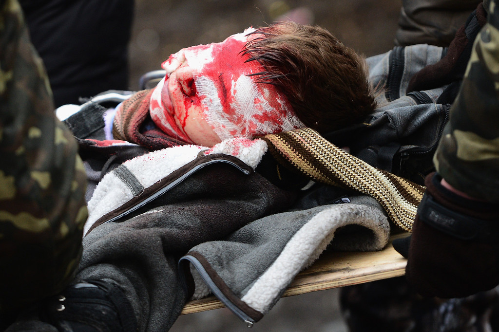 Description of . Anti-government protesters carry the injured during continued clashes with police in Independence square, despite a truce agreed between the Ukrainian president and opposition leaders on February 20, 2014 in Kiev, Ukraine.  (Photo by Jeff J Mitchell/Getty Images)