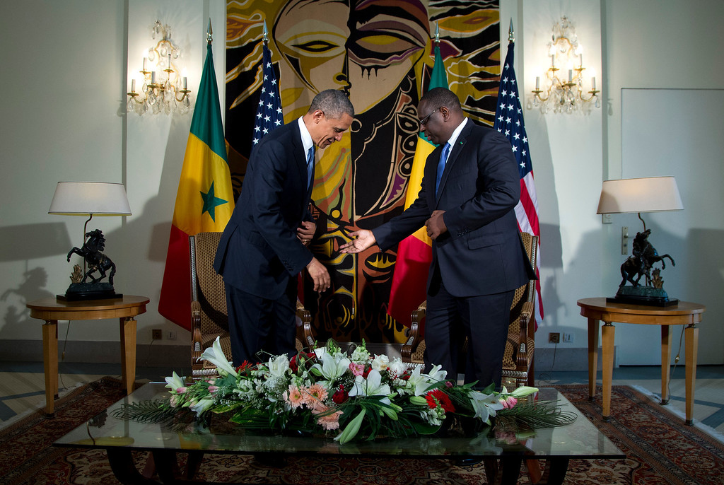 Description of . Senegalese President Macky Sall, right, gestures for U.S. President Barack Obama to sit during a bilateral meeting at the Presidential Palace on Thursday, June 27, 2013, in Dakar, Senegal. President Obama landed in Senegal Wednesday night to kick off a weeklong trip to Africa, a three-country visit aimed at overcoming disappointment on the continent over the first black U.S. president's lack of personal engagement during his first term. (AP Photo/Evan Vucci)
