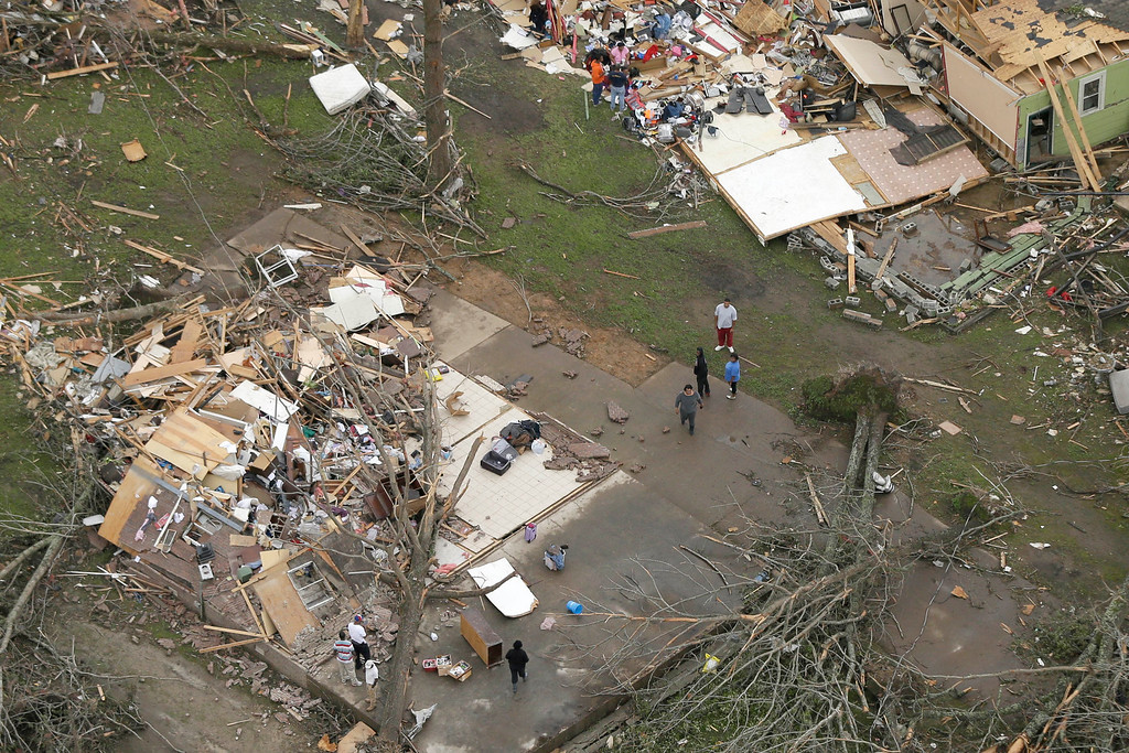 Description of . People walk between two destroyed houses in Mayflower, Ark., Monday, April 28, 2014, after a tornado struck the town late Sunday.  (AP Photo/Danny Johnston)