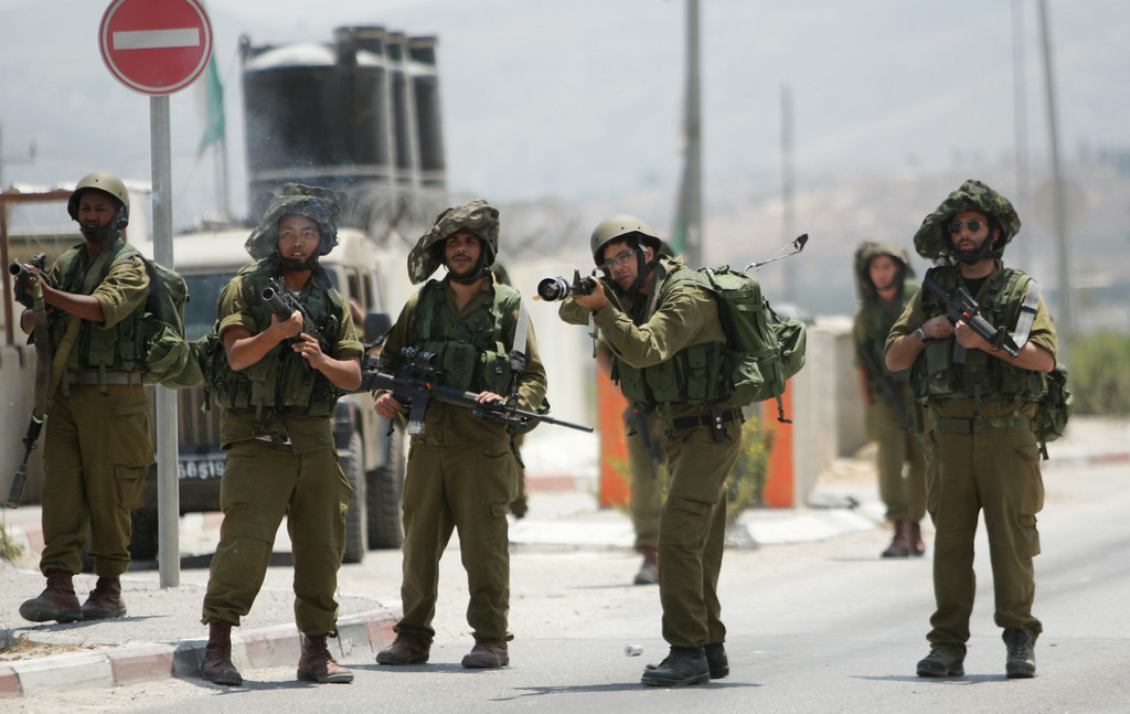 Description of . Israeli soldiers shoot tear gas towards Palestinian protesters during a demonstration against the Israeli military action in Gaza, at Hawara checkpoint near the West Bank city of Nablus, Tuesday, July 22, 2014. (AP Photo/Nasser Ishtayeh)