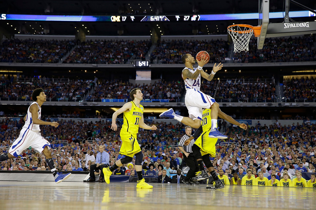 Description of . Kansas\' Travis Releford (24) shoots against Michigan during the first half of a regional semifinal game in the NCAA college basketball tournament, Friday, March 29, 2013, in Arlington, Texas. (AP Photo/David J. Phillip)