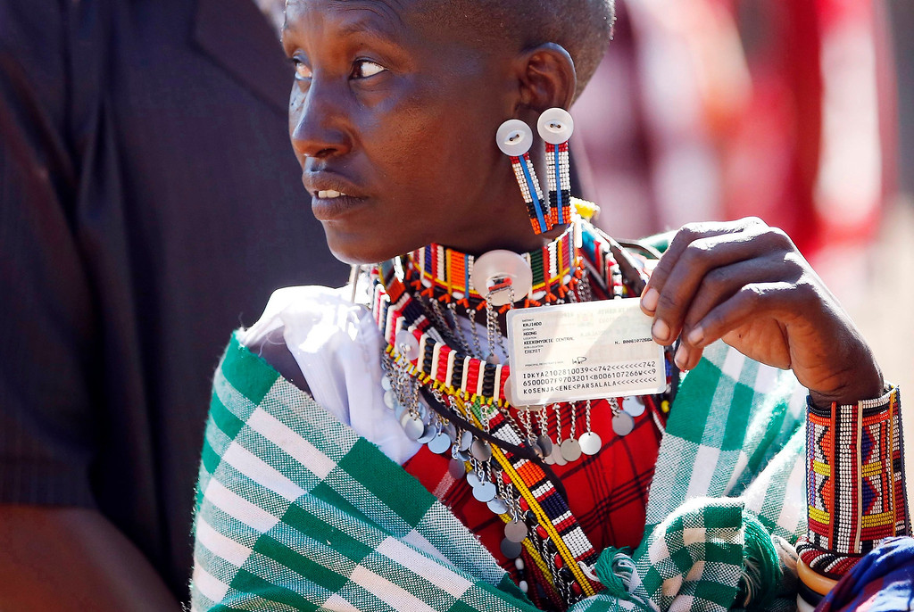 Description of . A Masai woman holds her ID card as she waits to cast her ballot in a polling station during the presidential and parliamentary elections near town of Magadi some 85 km (53 miles) south of Nairobi. REUTERS/Goran Tomasevic