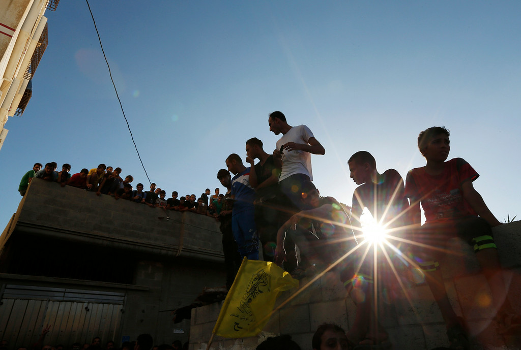 Description of . Palestinians watch as mourners carry the bodies of four boys killed in an Israeli strike, during their funeral in Gaza City on Wednesday, July 16, 2014. The four boys, who were cousins and ages 9 to 11, were killed while playing on a beach off a coastal road west of Gaza City, said Ashraf Al Kedra, a Palestinian doctor. Several others - adults and children - were wounded in the strike, he said. (AP Photo/Lefteris Pitarakis)