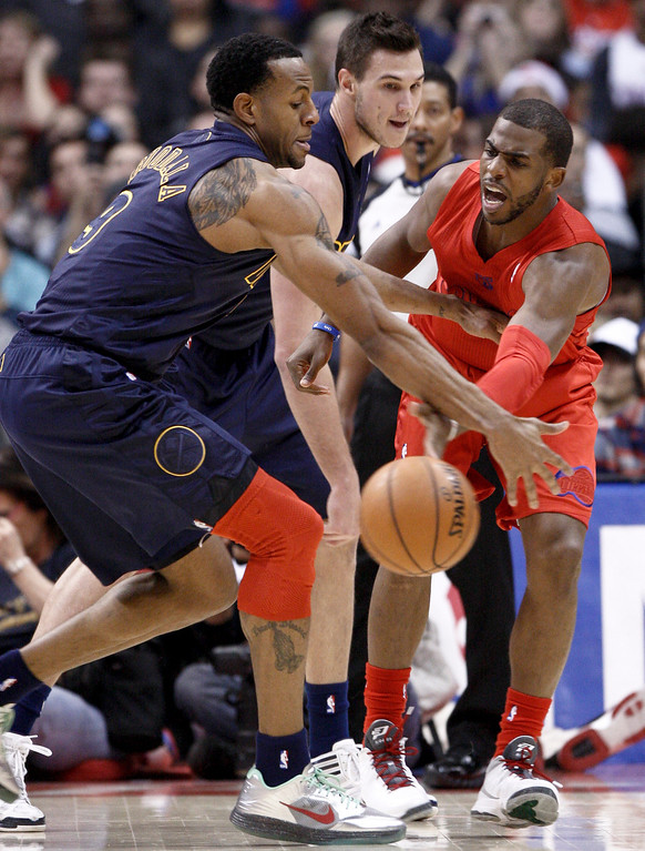 Description of . Los Angeles Clippers guard Chris Paul, right, passes the ball under pressure from Denver Nuggets' Andre Iguodala (9) and Danilo Gallinari, center, during the first half of their NBA basketball game, Tuesday, Dec. 25, 2012, in Los Angeles. (AP Photo/Jason Redmond)