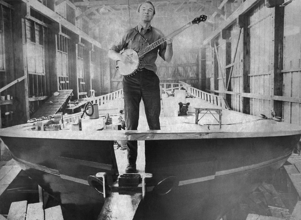 Description of . Folk singer Pete Seeger strums a banjo on the bow of the 75-foot Hudson River Sloop to be launched in South Bristol, Maine on May 14, 1969. Seeger and a group of volunteers had $150,000 vessel built to dramatize the fight against pollution of Hudson River Valley. (AP Photo/Stephen Nichols)