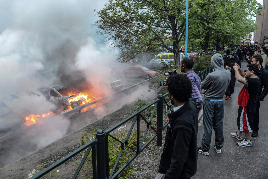 Description of . Bystanders take photos of a row of burning cars in the suburb of Rinkeby after youths rioted in several different suburbs around Stockholm, late May 23, 2013 in this picture provided by Scanpix. Hundreds of youth have torched cars and attacked police in four nights of riots in immigrant suburbs of Sweden's capital, shocking a country that dodged the worst of the financial crisis but failed to solve youth unemployment and resentment among asylum seekers.  REUTERS/Fredrik Sandberg/Scanpix