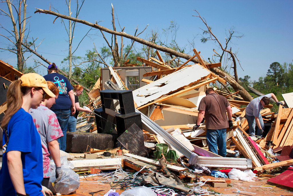 Description of . The Barnes family with the help of friends salvage what is left of their home that was damaged from severe weather on Tuesday, April 29, 2014 in Tupelo, Miss.  (AP Photo/Hunt Mercier)