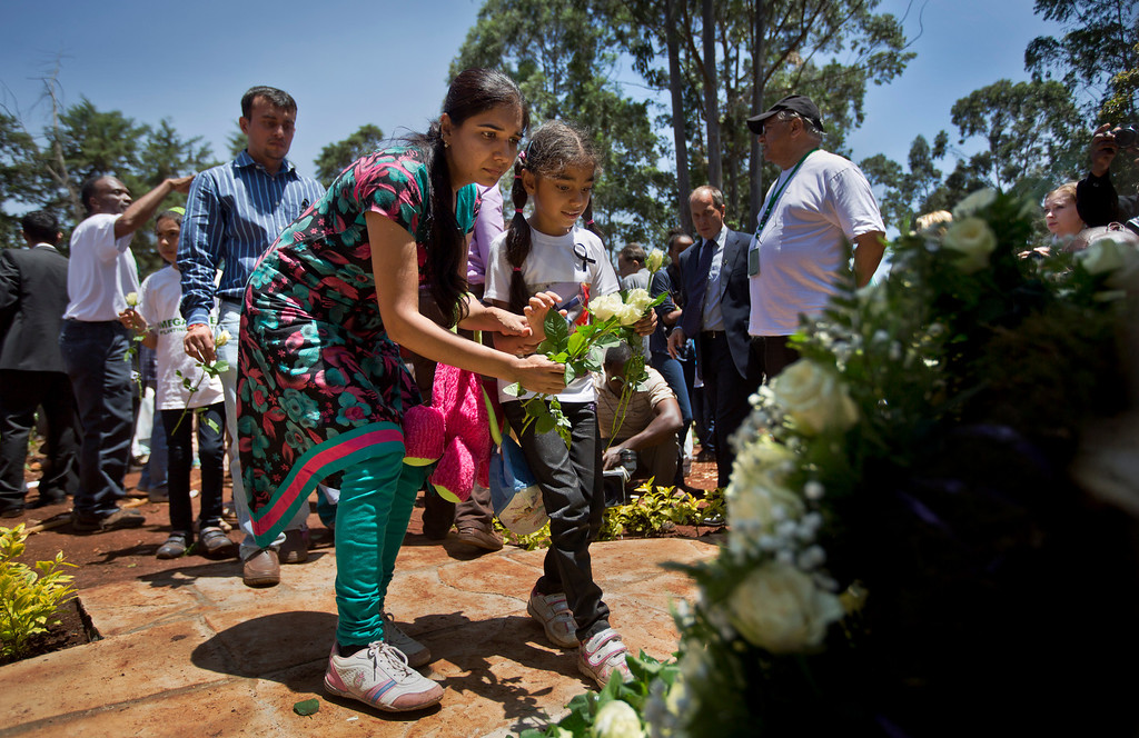 Description of . Relatives of those who died lay white roses at a stone memorial, during a memorial service marking the one-month anniversary of the the Sept. 21 Westgate Mall terrorist attack, in Karura Forest in Nairobi, Kenya Monday, Oct. 21, 2013. (AP Photo/Ben Curtis)