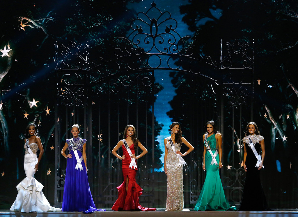 Description of . Miss Georgia USA Tiana Griggs, from left, Miss Louisiana USA Brittany Alyson Guidry, Miss Nevada USA Nia Sanchez, Miss Florida USA Brittany Oldehoff, Miss North Dakota USA Audra Mari and Miss Iowa USA Carlyn Bradarich, stand during the Miss USA pageant in Baton Rouge, La., Sunday, June 8, 2014. Sanchez would go on to win the Miss USA title. (AP Photo/Jonathan Bachman)