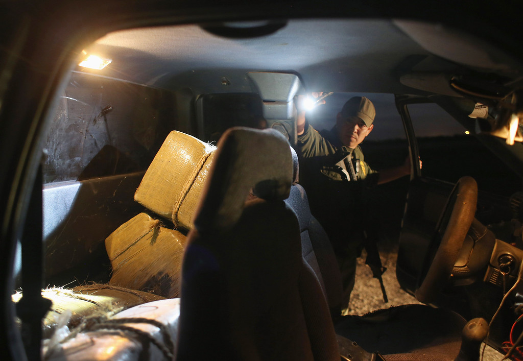 Description of . HIDALGO, TX - APRIL 10:  A U.S. Border Patrol Agent inspects a truckload of marijuana seized from drug smugglers near the U.S.-Mexico border on April 10, 2013 in Hidalgo, Texas. The agents, guided by helicopter surveillance from the U.S. Office of Air and Marine, waited more than four hours in hiding before seizing more than 900 pounds of the drug. The smugglers ran and escaped by swimming back across the Rio Grande River into Mexico. Border Patrol agents say they have also seen an additional surge in immigrant traffic since immigration reform negotiations began this year in Washington D.C. Proposed refoms could provide a path to citizenship for many of the estimated 11 million undocumented workers living in the United States.  (Photo by John Moore/Getty Images)