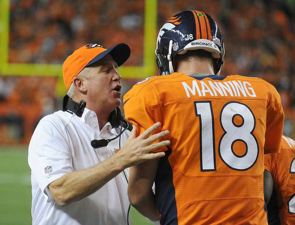 Description of . Denver Broncos head coach John Fox congratulates Denver Broncos quarterback Peyton Manning (18) after a touchdown in the second quarter.   (Photo by Tim Rasmussen/The Denver Post)