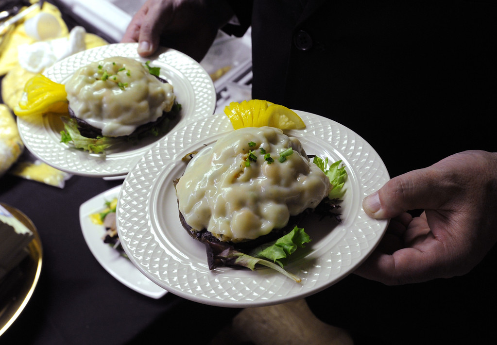 Description of . Red king crab stuffed portobello mushrooms are served to four-time Iditarod champion Martin Buser after he arrived first at the Yukon River in Anvik, Alaska, during the Iditarod Trail Sled Dog Race, early Friday, March 8, 2013. (AP Photo/Anchorage Daily News, Bill Roth)