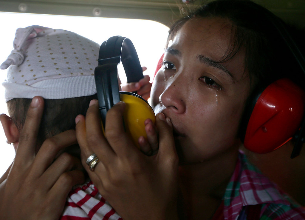Description of . A mother cries in relief upon boarding a Philippine Air Force helicopter, Monday Nov. 11, 2013 following Friday's typhoon Haiyan which lashed Guiuan township, Eastern Samar province, central Philippines. Typhoon Haiyan, one of the most powerful typhoons ever recorded, slammed into central Philippine provinces Friday leaving a wide swath of destruction and scores of people dead. (AP Photo/Bullit Marquez)