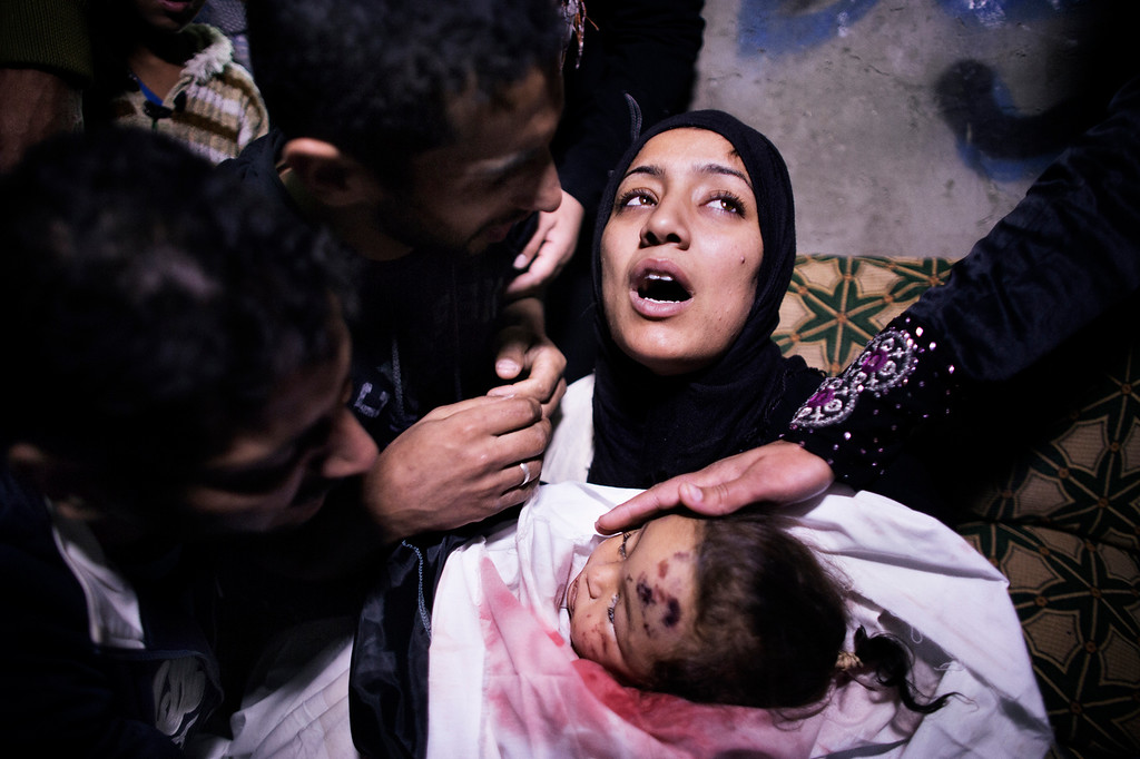 . The mother of 10-month-old Palestinian girl, Hanen Tafesh, killed the day before in an Israeli air strike, is comforted by her husband and relatives as she mourns before her funeral in Gaza City, on November 16, 2012. Israeli warplanes carried out multiple new air strikes on the Palestinian territory, including several hits on Gaza City, the third day of an intensive campaign which the military has said is aimed at stamping out rocket fire on southern Israel. (MARCO LONGARI/AFP/Getty Images)