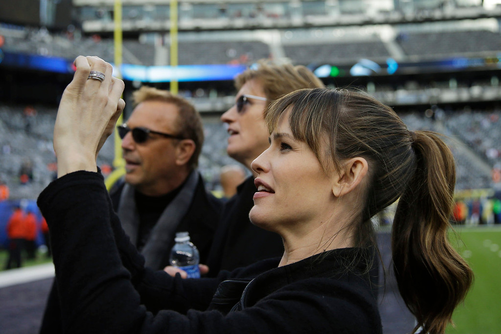 Description of . Actress Jennifer Garner takes a photo as actors Kevin Costner, left, and Denis Leary look on, at MetLife Stadium before the NFL Super Bowl XLVIII football game between the Seattle Seahawks and the Denver Broncos Sunday, Feb. 2, 2014, in East Rutherford, N.J. (AP Photo/Matt Slocum)