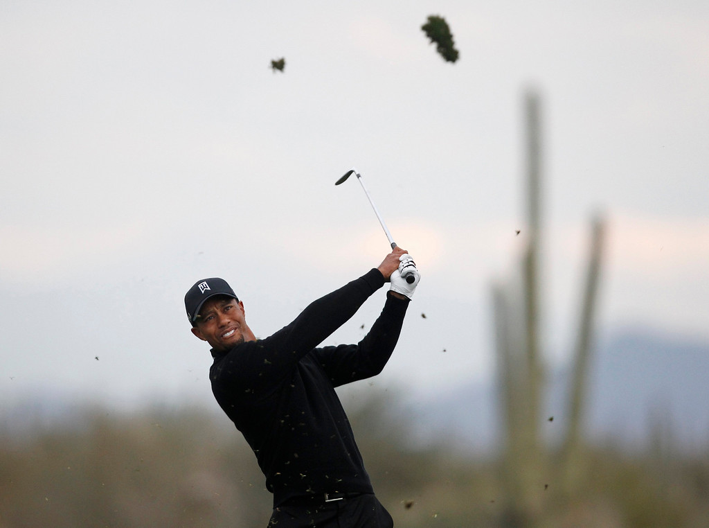 Description of . Tiger Woods of the U.S. hits a fairway shot on the 14th hole against Charlies Howell III of the U.S. during the weather-delayed first round of the WGC-Accenture Match Play Championship golf tournament in Marana, Arizona February 21, 2013. REUTERS/Matt Sullivan