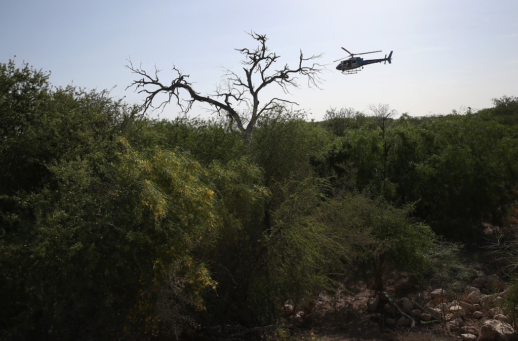 Description of . MISSION, TX - APRIL 11:  A U.S. Air and Marine helicopter searches for undocumented immigrants in thick brush near the U.S.-Mexico border on April 11, 2013 in Mission, Texas. Air and Marine agents helped U.S. Border Patrol Agents detain a group of 16 immigrants from Mexico and El Salvador said they crossed the Rio Grande River from Mexico into Texas during the morning hours before they were caught. The Rio Grande Valley sector of has seen more than a 50 percent increase in illegal immigrant crossings from last year, according to the Border Patrol. Agents say they have also seen an additional surge in immigrant traffic since immigration reform negotiations began this year in Washington D.C. Proposed refoms could provide a path to citizenship for many of the estimated 11 million undocumented workers living in the United States. Photo by John Moore/Getty Images)  (Photo by John Moore/Getty Images)