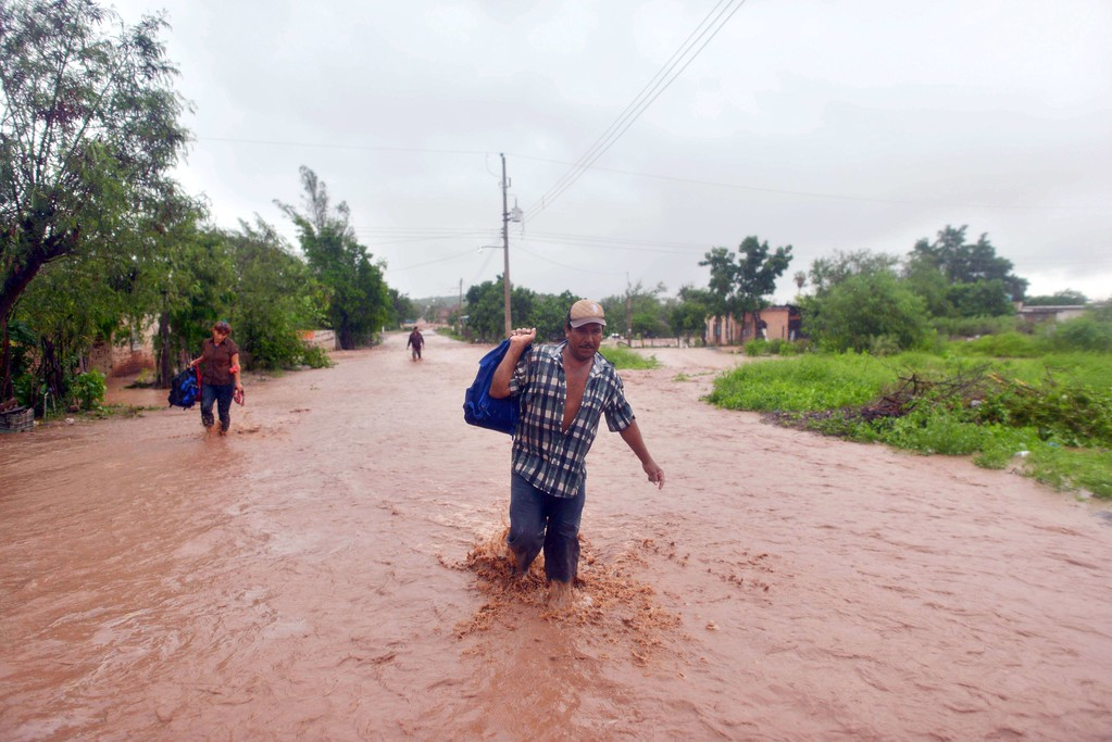 Description of . Residents of El Zapotillo evacuate their homes because of the overflooding of the neighboring river, in the state of Sinaloa, Mexico, on September 19, 2013. Deaths from floods and landslides battering Mexico neared 100 on Thursday as a fresh hurricane hit the northwest and rescuers faced a risky mission in a village buried in mud.  Fernando Brito/AFP/Getty Images