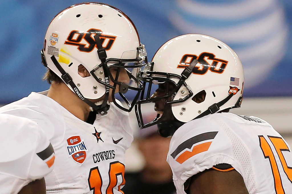 Description of . After scoring a touchdown against Missouri, Oklahoma State quarterback Clint Chelf (10) celebrates with wide receiver John Goodlett (15) during the second half of the Cotton Bowl NCAA college football game, Friday, Jan. 3, 2014, in Arlington, Texas. (AP Photo/Brandon Wade)