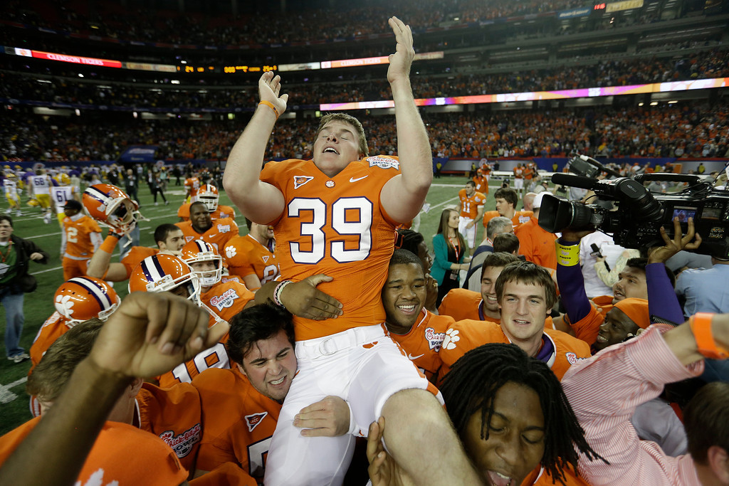 Description of . Clemson kicker Chandler Catanzaro (39) is hoisted into the air after he kicked the winning 37-yard field goal after the second half of the Chick-fil-A Bowl NCAA college football game against LSU, Monday, Dec. 31, 2012, in Atlanta. Clemson won 25-24.  (AP Photo/David Goldman)