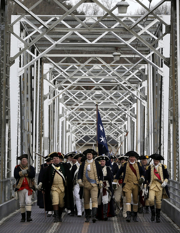 Description of . Gen. George Washington, played by John Godzieba, center, walks with his troops across a bridge after the group of re-enactors successfully crossed the Delaware River from Pennsylvania to New Jersey during the 61st annual re-enactment of Washington's daring Christmas 1776 crossing of the river, the trek that turned the tide of the Revolutionary War, in Washington Crossing, N.J. During the crossing 237 years ago, boats ferried 2,400 soldiers, 200 horses and 18 cannons across the river, and the troops marched eight miles downriver before battling Hessian mercenaries in the streets of Trenton. (AP Photo/Julio Cortez)