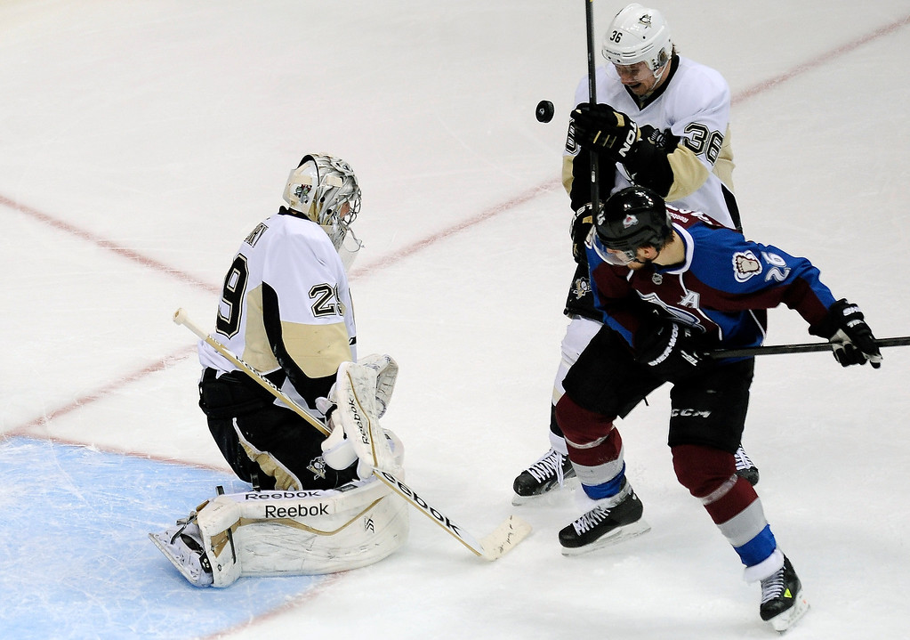 Description of . Pittsburgh Penguins left wing Jussi Jokinenl, top right, of Finland, and Colorado Avalanche center Paul Stastny fight for position as the puck rebounds off Pittsburgh Penguins goalie Marc-Andre Fleury, left, during the first period of an NHL hockey game Sunday, April 6, 2014, in Denver. (AP Photo/Chris Schneider)