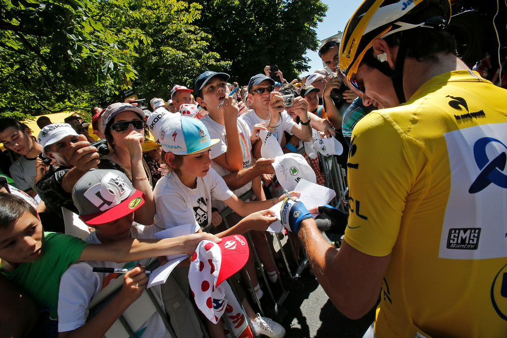 Description of . Daryl Impey of South Africa, wearing the overall leader's yellow jersey, signs autographs prior to the start of stage eight of the Tour de France cycling race over 195 kilometers (122 miles) with start in Castres and finish in Ax 3 Domaines, Pyrenees region, France, Saturday July 6 2013. (AP Photo/Christophe Ena)
