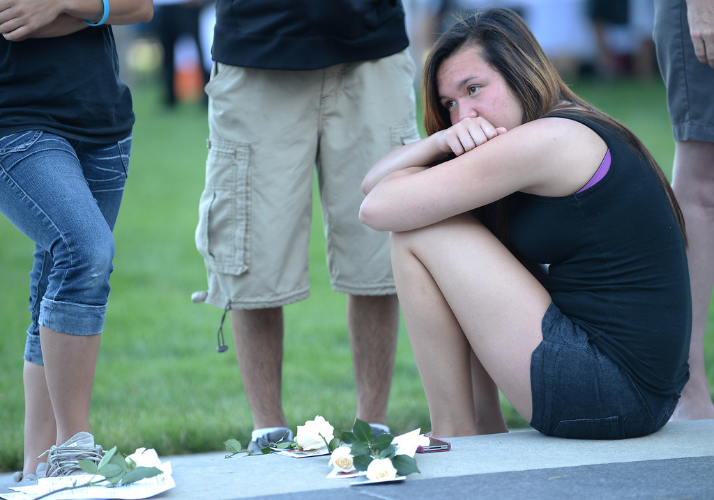 Description of . AURORA, CO. - July 20: Jessica Almand, 16, of Cherokee Trail High School attends a day of remembrance at the Aurora Municipal Center. Aurora, Colorado. July 20, 2013. People gathered outside the Aurora Municipal Center to mark the first anniversary of the deaths of 12 people and the injury of at least 70 others in a mass shooting that forever changed an entire community. (Photo By Hyoung Chang/The Denver Post)