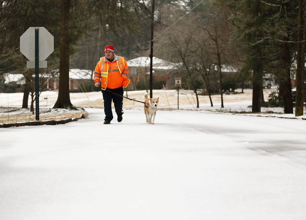 Description of . Professional pet sitter Edward Forrester walks a neighbor\'s dog during a severe winter storm in Avondale Estates, Georgia, USA, 12 February 2014. Ice and snow in the metro Atlanta area and north Georgia is expected to make travel treacherous and cut electricity to thousands of customers.  EPA/ERIK S. LESSER